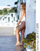 Купить «Attractive girl in swimsuit standing near hotel wall at ocean shore», фото № 28917699, снято 10 июля 2018 г. (c) Яков Филимонов / Фотобанк Лори