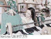 Купить «Woman customer choosing green striped long sleeve shirt in store», фото № 28917771, снято 15 марта 2018 г. (c) Яков Филимонов / Фотобанк Лори