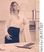Купить «Kindly girl with an outstretched hand is standing near table», фото № 28917827, снято 17 октября 2017 г. (c) Яков Филимонов / Фотобанк Лори