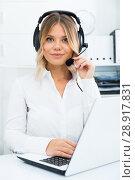 Купить «Young girl in call center with headphones sitting with laptop», фото № 28917831, снято 17 октября 2017 г. (c) Яков Филимонов / Фотобанк Лори