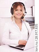 Купить «Young call center employee in headphones is sitting near laptop», фото № 28917835, снято 17 октября 2017 г. (c) Яков Филимонов / Фотобанк Лори