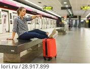 Купить «Girl sitting with legs on suitcase at metro station», фото № 28917899, снято 27 апреля 2018 г. (c) Яков Филимонов / Фотобанк Лори