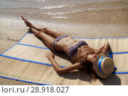 Купить «Getting golden tan. Full length top view of beautiful young woman in swimwear covering face with hat while sunbathing on the beach sea, time to travel», фото № 28918027, снято 4 августа 2018 г. (c) Happy Letters / Фотобанк Лори