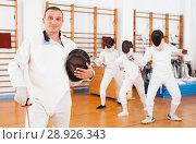 Купить «Active young male fencer in uniform standing with mask and foil at fencing room», фото № 28926343, снято 11 июля 2018 г. (c) Яков Филимонов / Фотобанк Лори