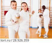 Купить «Woman fencer practicing new movements with trainer at fencing room», фото № 28926359, снято 11 июля 2018 г. (c) Яков Филимонов / Фотобанк Лори