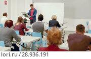 Купить «Smiling male teacher giving presentation for students in lecture hall», видеоролик № 28936191, снято 23 мая 2018 г. (c) Яков Филимонов / Фотобанк Лори