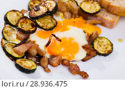 Купить «Plate with scrambled eggs with lard and zucchini at table on table», фото № 28936475, снято 17 августа 2018 г. (c) Яков Филимонов / Фотобанк Лори