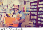 Купить «Workman holding basket with picked tools in paint store», фото № 28938035, снято 13 сентября 2017 г. (c) Яков Филимонов / Фотобанк Лори