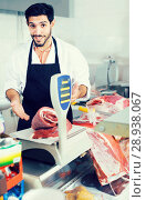 Купить «Man butcher is weighing meat in the market.», фото № 28938067, снято 15 сентября 2017 г. (c) Яков Филимонов / Фотобанк Лори