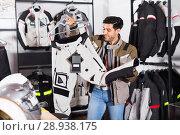 Купить «Male customer is choosing modern trousers in the sport store.», фото № 28938175, снято 1 сентября 2017 г. (c) Яков Филимонов / Фотобанк Лори