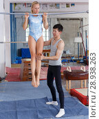 Купить «Man and woman doing acrobatic exercises in gym», фото № 28938263, снято 18 июля 2018 г. (c) Яков Филимонов / Фотобанк Лори