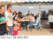 Купить «Guests in a street cafe on the Black Sea», фото № 28943451, снято 23 августа 2016 г. (c) Caro Photoagency / Фотобанк Лори