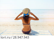 Купить «Summer lifestyle portrait of pretty young suntanned woman in a hat. Enjoying life and sitting on the beach, time to travel. Looking at the sea», фото № 28947943, снято 4 августа 2018 г. (c) Happy Letters / Фотобанк Лори