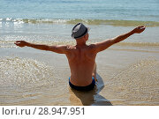 Купить «Summer lifestyle portrait of pretty young suntanned man in a hat. Enjoying life and sitting on the beach, time to travel. Looking at the sea», фото № 28947951, снято 4 августа 2018 г. (c) Happy Letters / Фотобанк Лори
