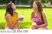 Купить «teenage girls drink milk shakes at picnic in park», видеоролик № 28954199, снято 1 августа 2018 г. (c) Syda Productions / Фотобанк Лори