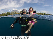 Купить «Mother with diving equipment and child with life jacket (both model released) in sea with Mt Agung volcano in background, Tulamben, east Bali, Indonesia.», фото № 28956579, снято 13 мая 2018 г. (c) age Fotostock / Фотобанк Лори