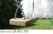 Купить «White Wedding dress hanging on a green swing in the garden», видеоролик № 28957791, снято 9 августа 2018 г. (c) Aleksejs Bergmanis / Фотобанк Лори