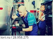 Купить «Mechanic man working with tire», фото № 28958275, снято 19 сентября 2019 г. (c) Яков Филимонов / Фотобанк Лори