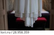 Купить «White wedding dress hanging in the doorway in the castle the day before the ceremony», видеоролик № 28958359, снято 8 августа 2018 г. (c) Aleksejs Bergmanis / Фотобанк Лори