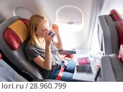 Купить «Woman drinking coffee on commercial passengers airplane during flight.», фото № 28960799, снято 10 июля 2020 г. (c) Matej Kastelic / Фотобанк Лори