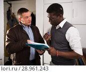 Купить «Two men holding folder with documents, talk about services», фото № 28961243, снято 26 февраля 2018 г. (c) Яков Филимонов / Фотобанк Лори