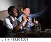 Купить «Positive male interracial friends watching football match on tv», фото № 28961359, снято 26 февраля 2018 г. (c) Яков Филимонов / Фотобанк Лори
