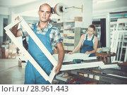 Купить «Workman in workwear is standing with window frame from pvc profile», фото № 28961443, снято 19 июля 2017 г. (c) Яков Филимонов / Фотобанк Лори
