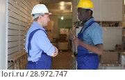 Купить «Two male builders working at indoors building site», видеоролик № 28972747, снято 21 мая 2018 г. (c) Яков Филимонов / Фотобанк Лори
