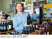 Купить «customer picking bottle in wine store», фото № 28973867, снято 20 мая 2019 г. (c) Яков Филимонов / Фотобанк Лори