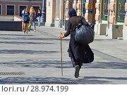 Женщина без определенного места жительства в темной одежде со спины с деревянной палкой в центре Москвы (2018 год). Редакционное фото, фотограф Овчинникова Ирина / Фотобанк Лори