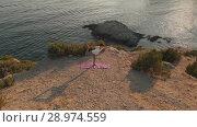 Купить «Woman doing yoga at sunset», видеоролик № 28974559, снято 20 июля 2018 г. (c) Илья Шаматура / Фотобанк Лори