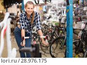Купить «Female is standing with bicycle in sport store», фото № 28976175, снято 13 сентября 2017 г. (c) Яков Филимонов / Фотобанк Лори