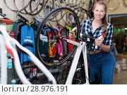 Купить «Young positive woman is standing with bicycle», фото № 28976191, снято 13 сентября 2017 г. (c) Яков Филимонов / Фотобанк Лори