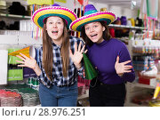 Attractive girls trying on party hats in festive accessories shop. Стоковое фото, фотограф Яков Филимонов / Фотобанк Лори