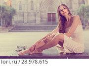 Купить «portrait of young adult girl in evening apparel sitting with sandals in european town», фото № 28978615, снято 24 июня 2017 г. (c) Яков Филимонов / Фотобанк Лори