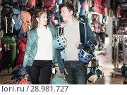 Купить «active girl and guy select gear for hiking and camping in sports shop», фото № 28981727, снято 25 октября 2017 г. (c) Яков Филимонов / Фотобанк Лори