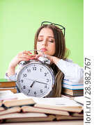 Купить «Young female student preparing for exams with many books in time», фото № 28982767, снято 8 июня 2018 г. (c) Elnur / Фотобанк Лори