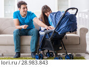 Купить «The young parents with their newborn baby in baby pram sitting on the sofa», фото № 28983843, снято 22 ноября 2017 г. (c) Elnur / Фотобанк Лори