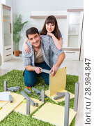 Купить «The young family assembling furniture at new house», фото № 28984847, снято 3 апреля 2018 г. (c) Elnur / Фотобанк Лори