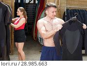 Купить «Glad guy surfer choosing surfing suit for rent», фото № 28985663, снято 30 апреля 2018 г. (c) Яков Филимонов / Фотобанк Лори