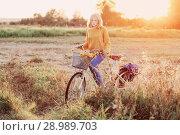 Купить «teenager girl on bike in summer field at sunset», фото № 28989703, снято 22 августа 2018 г. (c) Майя Крученкова / Фотобанк Лори