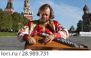 Купить «The musician in traditional Russian clothes plays an old Russian musical instrument gusli on the background of the Kremlin and St. Basil's Cathedral on red Square. Moscow, Russia», видеоролик № 28989731, снято 25 августа 2018 г. (c) Алексей Кузнецов / Фотобанк Лори