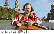 Купить «The musician in traditional Russian clothes plays an old Russian musical instrument gusli on the background of the Kremlin on red Square in Moscow, Russia», видеоролик № 28990511, снято 25 августа 2018 г. (c) Алексей Кузнецов / Фотобанк Лори