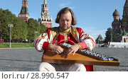 Купить «Folk performer in traditional Russian clothes plays an old Russian musical instrument gusli on the background of the Kremlin and St. Basil's Cathedral on red Square. Moscow, Russia», видеоролик № 28990547, снято 26 августа 2018 г. (c) Алексей Кузнецов / Фотобанк Лори