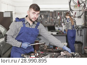 Купить «Male master is choosing instruments in workshop», фото № 28990895, снято 18 декабря 2017 г. (c) Яков Филимонов / Фотобанк Лори