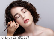 Купить «Make-up artist apply beauty makeup on the eyelids of a beautiful girl. Visagist with makeup brush in hand», фото № 28992559, снято 22 марта 2018 г. (c) Serg Zastavkin / Фотобанк Лори
