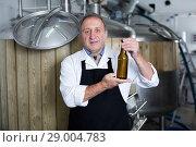 Купить «Adult brewer is standing with beer bottle», фото № 29004783, снято 18 сентября 2017 г. (c) Яков Филимонов / Фотобанк Лори