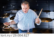 Купить «Musician male is choosing drum set and playing on it in music shop.», фото № 29004827, снято 18 сентября 2017 г. (c) Яков Филимонов / Фотобанк Лори