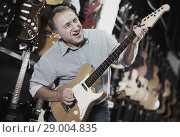 Купить «Male is playing on electric guitar», фото № 29004835, снято 18 сентября 2017 г. (c) Яков Филимонов / Фотобанк Лори