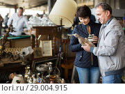 Купить «cheerful mature spouses buying retro handicrafts on flea market», фото № 29004915, снято 23 октября 2017 г. (c) Яков Филимонов / Фотобанк Лори